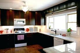 light brown kitchen cabinets white kitchen cabinets with black appliances beige ceramic tile floor modern light