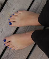 blue nail varnish polish on a mans toes