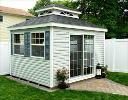 white trim rustic black shingles and double roof sunbursts 6 single pane windows with pacific blue shutters and sliding glass door
