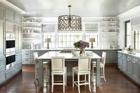a vintage light fixture hangs over the island which is surrounded by counter stools from hickory chair cake stands and wine glasses are displayed on the