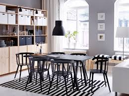 A large dining room with a black dining table and six chairs combined with  storage in