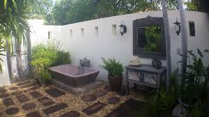 ... dazzling outside bathroom with stone pavers and white concrete fence  also antique vanity ...
