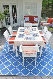 a gorgeous 9 x 12 blue outdoor rug decorates a backyard deck in a patio makeover