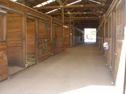 inside smaller barn wash rack stall water system non slip asphalt floor sky lights strength rubber mats atop gravel drainage system per