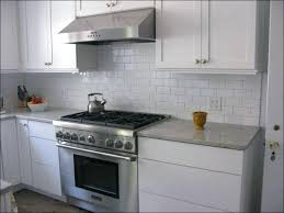grey glass subway tile backsplash with cherry cabinets and black countertops
