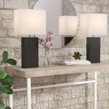 these fashionable table ls with their genuine leather bos and white fabric shades will add style and pizzazz to any room they believe that lighting