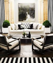 to add a pop of color to a black and white living room try placing houseplants on either side of your couch
