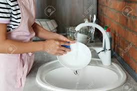 Woman Washing Dishes In Kitchen Sink Closeup View Cleaning Stock
