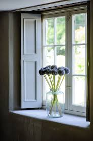 Large cottage window with pale wooden shutters.To top it of a clear large  vase with dark Alliums sits on the sill.