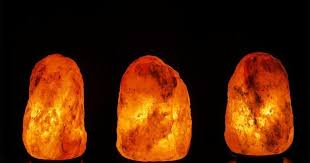 three salt lamps on black background