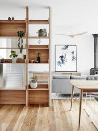 a modern wooden shelving unit features open and box shaped shelves with much potted greenery for