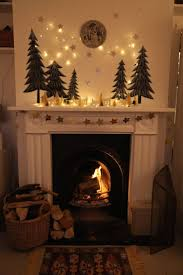 mantel lighting. hearth mantel evergreen trees moon ceramic house lanterns string lights garland lighting t