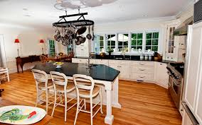 A beautiful kitchen with a kitchen island with potrack, a sink and seating