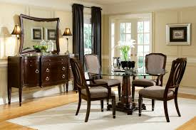 material round gl dining table carved brown pedestal base dark room wooden chairs with grey seat white