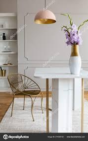 Blumen Auf Weißen Marmor Tisch Der Nähe Von Gold Stuhl Stockfoto