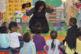 is tfa for you teach for america a young female teacher curly black hair smiles as she gives a puppet show to