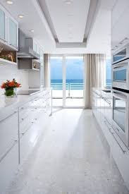 narrow white kitchen design with white granite flooring and white kitchen cabinet under ceiling recessed lighting