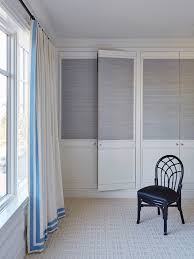 master bedroom features a wall of built in closet cabinets finished with bi fold doors clad in gray grasscloth wallpaper next to windows dressed in white