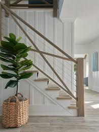 morgan harrison home a fiddle leaf fig plant in a woven planter sits in front of a staircase boasting stained wood treads covered in a natural woven
