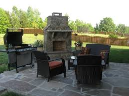 decorative small stone outdoor wood burning fireplace in backyard with living area and portable grille
