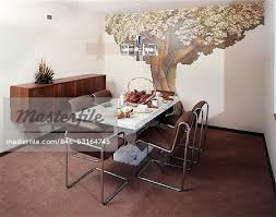 1970s dining room table chairs wall decor mural of tree stock photo