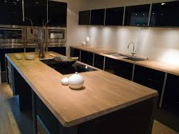 trendy modern kitchen with high gloss black cabinets and wood butcher block wood countertops