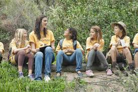 c counsellor and children sitting on log in forest
