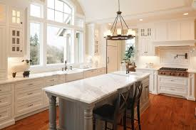 beautiful white kitchen cabinets: large ceiling height window affords natural light in this white kitchen centered around large marble topped