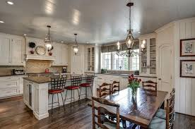 white country kitchen with recessed panel cabinets black granite counters dining island and dark