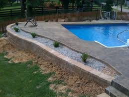 inground pool with retaining wall | An inground liner pool with a stamped  concrete pool deck