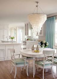 large capiz shell chandelier over white dining table and chairs in chic dining room