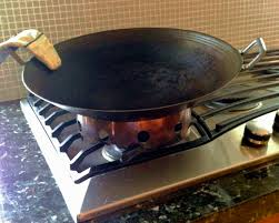 lightweight thin walled round bottom cast iron wok sits on wok ring on top