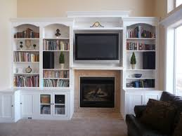 black steel fireplace with brown frame and television above between white wall shelves for books plus