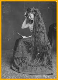 mrs frton combing her long hair with the help of a mirror circa 1885