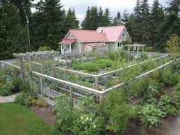 an artfully designed double fence each 5 ft high with a 5 ft space between keeps deer from jumping into the vegetable garden and also provides an