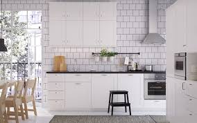 A white medium size kitchen with black worktops, handles and knobs.  Combined with stainless