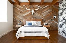 reclaimed wood wall with chevron pattern steals the show in this bedroom design studio