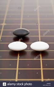 Game With Stones And Wooden Board three stones during go game playing on wooden board close up Stock 75