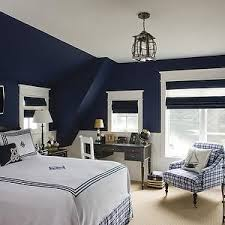 Navy blue attic boy's room features navy walls highlighting a small window  dressed in a dark woven shade to the right of a West Elm Parsons Desk with  ...