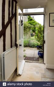 an open front door of a period cote looking from the inside out onto a garden