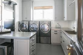 light gray laundry room cabinets with stainless steel countertops