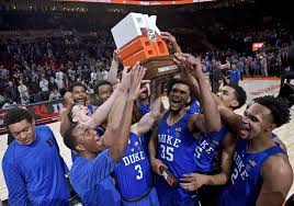 duke holds up the chionship trophy after an ncaa college basketball game against florida in the