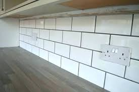 cream tiles white grout subway tile dark kitchen