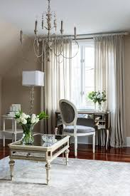 the bedroom also has a console table and a elegant chair lighted by chandelier and lamp