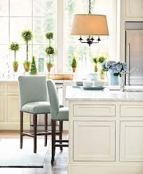 a linen drum pendant stands over an ivory kitchen island topped with carrera marble lined with blue linen nailhead counter stools