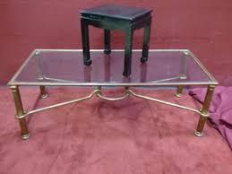 1 Table basse en métal doré et patiné à plateau de verre...