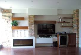 extremely cool white floating fireplace cabinet with open shelves as crafts display as well as brick