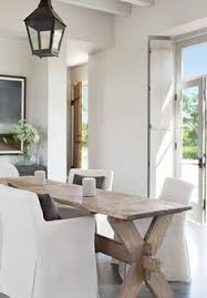 this dining room with antique rustic orchard table slipcovered dining chairs and simple lantern