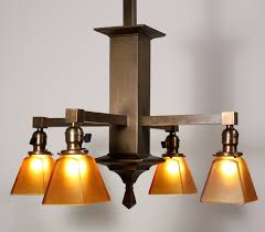 a splendid antique brass four light chandelier dating from the early 1900 s with amber glass shades this arts and crafts chandelier begins with a square