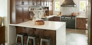 kitchen with brown cabinetry and cream color quartz countertops and large tile floors
